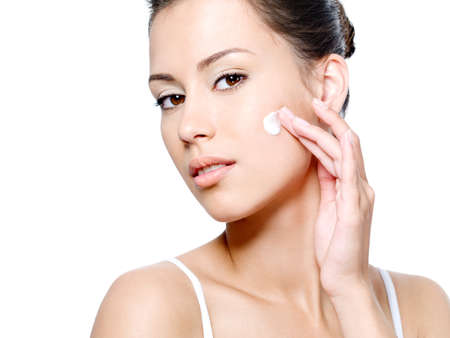 Beautiful woman with sensual look applying cream on her clean face - white background photo