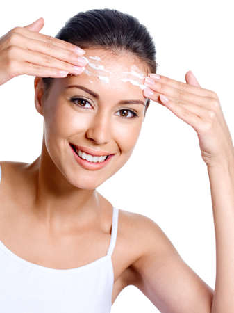 woman face cream: Portrait of beautiful happy woman applying cream on her forehead - white background