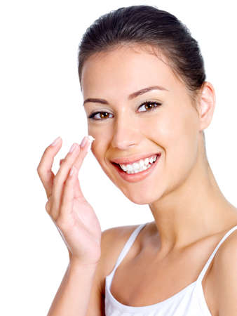 woman face cream: Happy smiling beauitful woman applying moisturizer cream on the face Stock Photo
