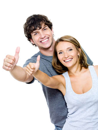 pretty people: Two young smiling people with thumbs-up gesture isolated on white