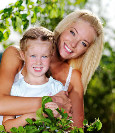 Happy portrait of the mother and little daughter outdoors photo