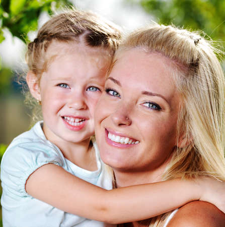 Happy faces of the young  mother and  little girl outdoor photo