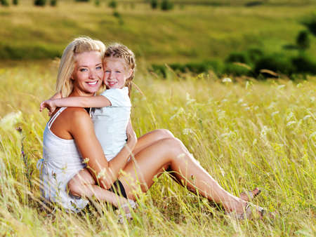 mother with child: Happy portrait of the mother and little daughter on meadow