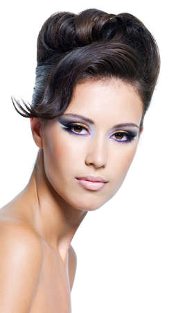 Beautiful face of a glamour woman with modern curly hairstyle and colored makeup photo
