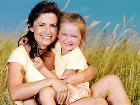 mama e hija: Madre sonriente e hija poco sobre la naturaleza. Gente feliz al aire libre  Foto de archivo
