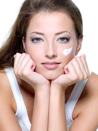 Beautiful woman applying moisturizer cream on face - on a white photo