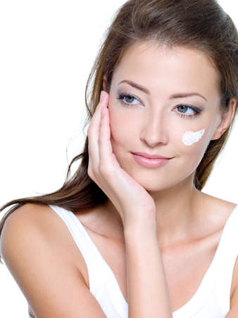 Beautiful woman with moisturizer cosmetic cream on face - on a white Stock Photo