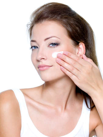 Beautiful woman applying moisturizer cosmetic cream on face - on a white Stock Photo - 7506947