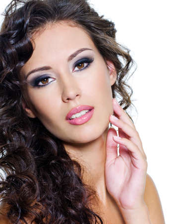 Beautiful face of young woman with clean skin. Girl with long curly hairs. Bright eye make-up