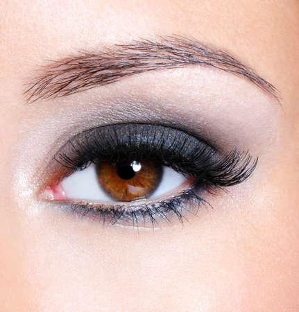 pesta�as postizas: Ojo femenino con maquillaje de glamour marr�n oscuro-macro disparo