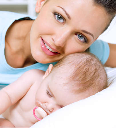 Portrait of a happy young mother near sleeping baby  photo