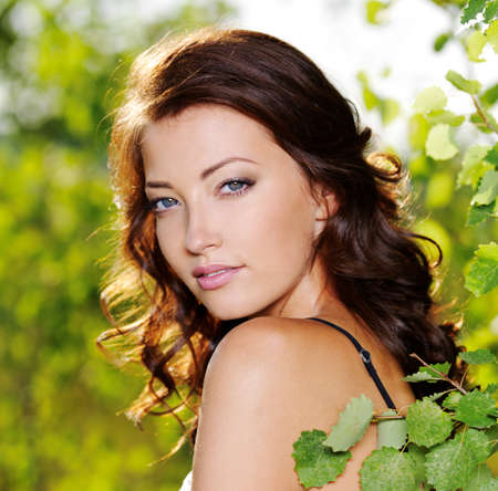 Beautiful face of the young sexy woman posing near the green tree on nature photo