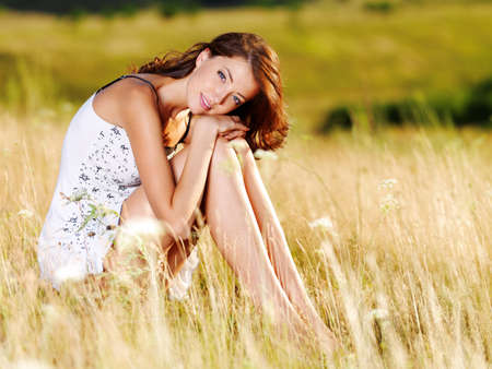 Beautiful  sexy caucasian woman sitting on the grass on summer meadow photo
