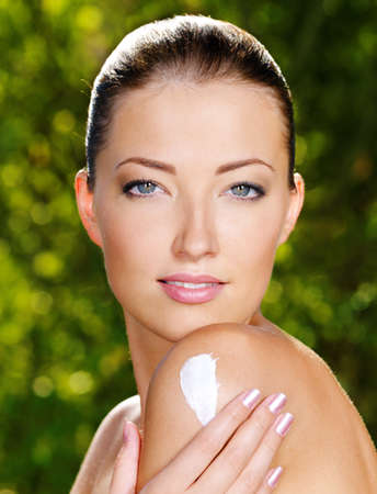 Beautiful sexy woman with fresh health skin applying cream on shoulder. Outdoors Stock Photo