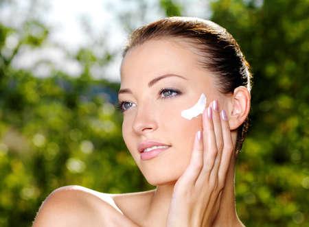 Beautiful sexy woman with fresh health skin applying cream on cheek. Adult girl on nature