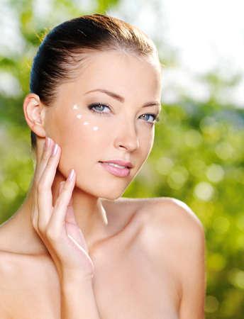Beautiful sexy woman applying cosmetic cream on skin near eyes - Outdoors photo