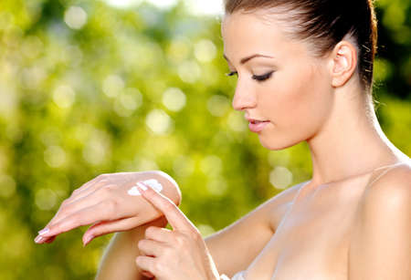 cream and green:  beautiful woman applying on hand cosmetic cream. Green natural background
