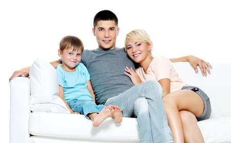 Happy young smiling family with kid sitting on white sofa - Isolated photo