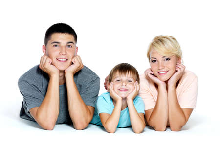 lying down on floor: Happy young smiling family with little boy  - isolated Stock Photo
