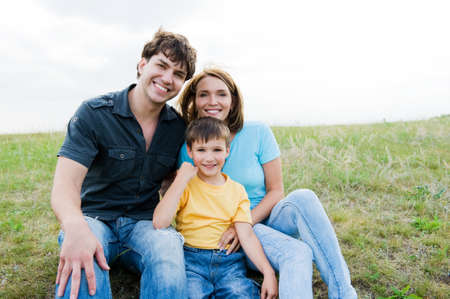 Happy beautiful young family posing outdoors. Three people photo