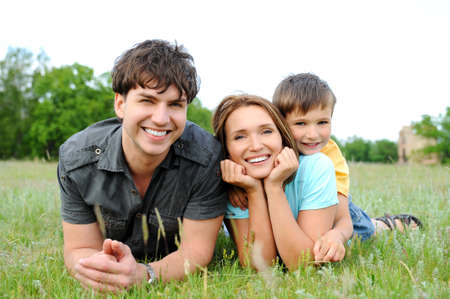 happy family nature: Happy beautiful young family lying on the  green grass. Three cheerful person