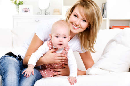 01: Portrait of young happy mother with newborn baby at home