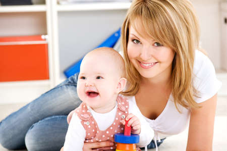 Beautiful baby playing with toys with happy mother  indoors Stock Photo