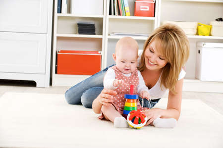 child care: Beautiful baby playing with toys with happy mother  indoors Stock Photo