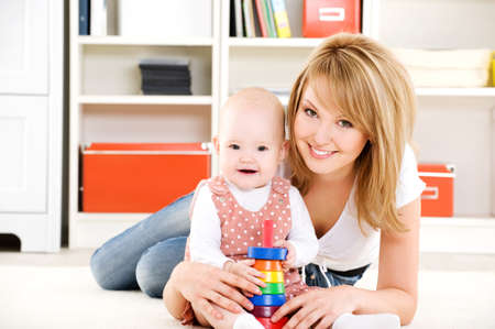 mum and baby: Beautiful baby playing with toys with happy mother  indoors Stock Photo