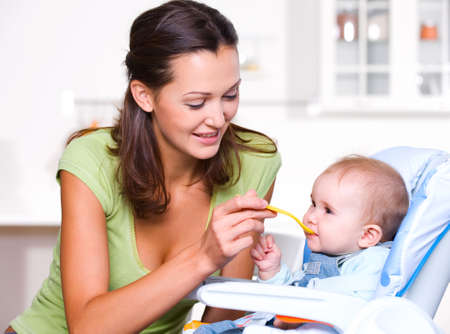 Mother feeding hungry baby in the highchair indoors Stock Photo - 7817361
