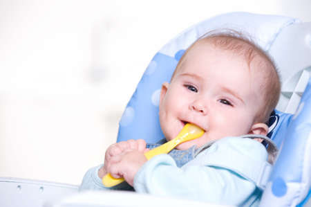 highchair: Beautiful happy baby with spoon sitting on highchair Stock Photo