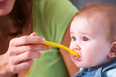 Mother feeding hungry baby from spoon in the highchair indoors  photo
