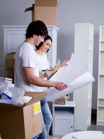 Happy young couple in their new flat with plan in their hands Stock Photo - 7917574