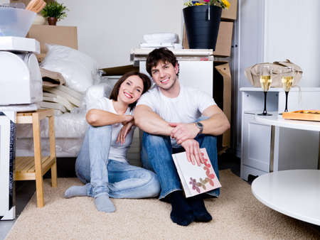 'young things': Young happy smiling couple sitting on the floot in the flat after moving