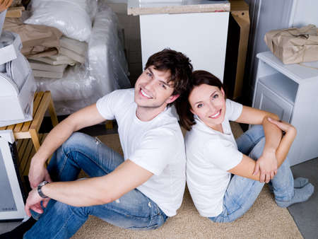woman sitting floor: Smiling happy young couple sitting back-to-back after moving - high angle Stock Photo