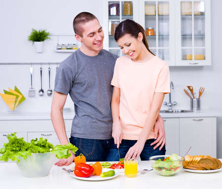 Happy young couple making a breakfast together in the kitchen photo