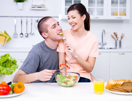 woman eat: Loving happy couple eating salad in the kitchen - indoors Stock Photo