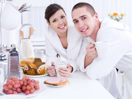 Portrait of beautiful young smiling couple having breakfast in the kithen photo
