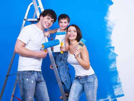 Friendly smiling family with young son painting the wall photo