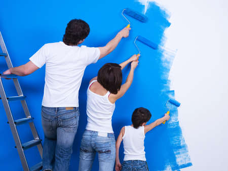 Friendly family brushing the wall together into the blue color photo