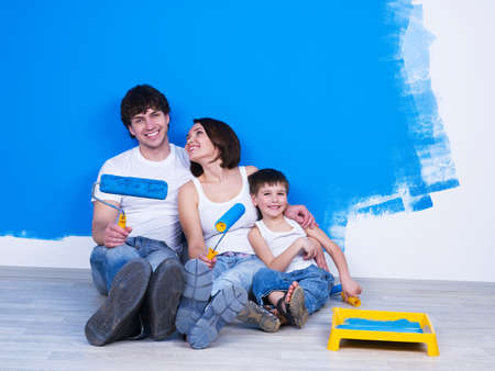 Happy young family with little son sitting near the wall with paintbrush photo