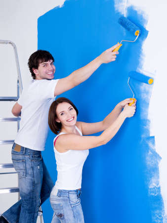 Portrait of happy smiling couple brushing the wall - indoors photo