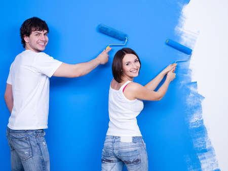 home improvement: Renovation by happy young cheerful couple brushing the wall