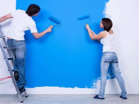 house renovation: Coloring the wall in blue by young couple in casuals - horizontal Stock Photo