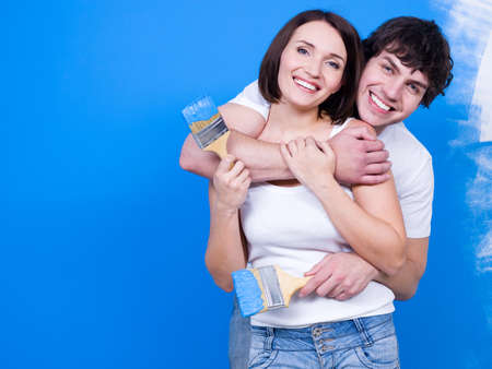 Loving happy couple standing in embrace with paintbrush near the wall Stock Photo
