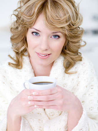 Close-up portrait of beautiful young woman holding cup of coffee photo