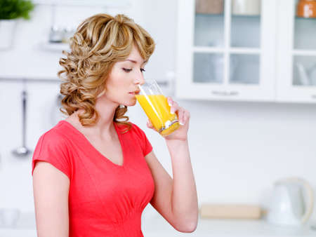 Beautiful young womsn with a glass of fresh orange juice in the kitchen photo
