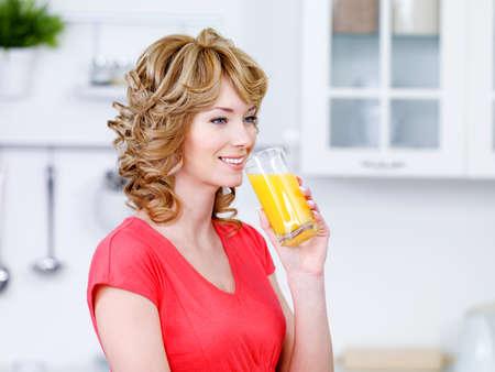 Beautiful smiling woman drinking fresh orange juice - indoors photo