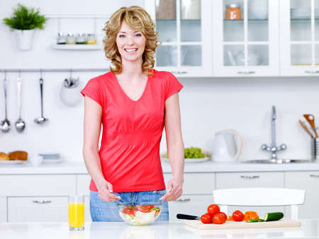 Beautiful young woman cooking healthy food in the kitchen - indoors Stock Photo - 7917547