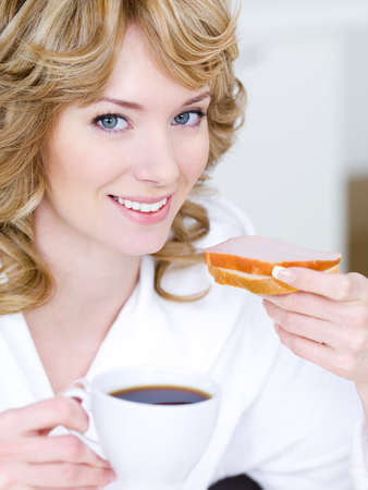 Close-up portrait of happy smiling beautiful woman eaitng sandwich and drinking coffee photo